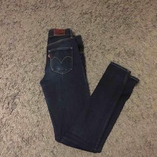 Mörkblå Levis jeans i modell High Rise skinny, Storlek 25. Något slitna men inga hål eller liknande.