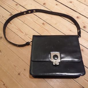 Svart väska i lagom storlek med silverdetaljer och två separata fack + ett mindre fack med dragkedja inuti. I bra skick!