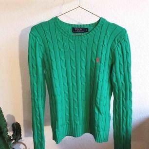 Kabelstickad tröja från POLO RALPH LAUREN. Grön med röd logga, rundad halsringning. Mycket fint skick. Kommer från ett djur- & rökfritt hem.