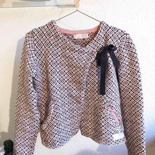 Stickad tröja från ODD MOLLY. Rosa/vit/grå med fint mönster. Försluts med knapp & knyte över vänster bröst. Använd ett fåtal gånger & är i mycket fint skick. Kommer från ett djur- & rökfritt hem. Nypris ca 1899kr