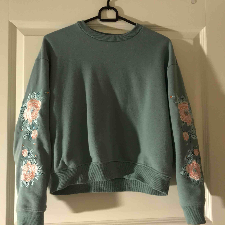 Grön lite croppad tröja från forever 21 men broderi på armarna. Nyskick. Köparen står för frakt . Huvtröjor & Träningströjor.