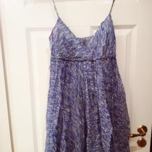 Underbar blå/vit mönstrad klänning från Ayres. Smala justerbara axelband och täckta knappar i ryggen. Ljusblått undertyg.