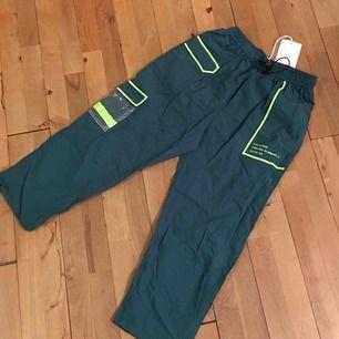 Trendiga cargo byxor som är helt helt nya med tagg på. Köpa i Korea, PVC fickor , neon grön, byxan är mörk grön