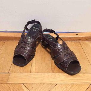 Knappt använda finskor / sandaler i brunt äkta läder, rem bak med spänne för bra passform. Bekväm låg klack. Bra kvalitet.  Har Swish. Kan skickas mot frakt. Rökfritt & djurfritt hem.