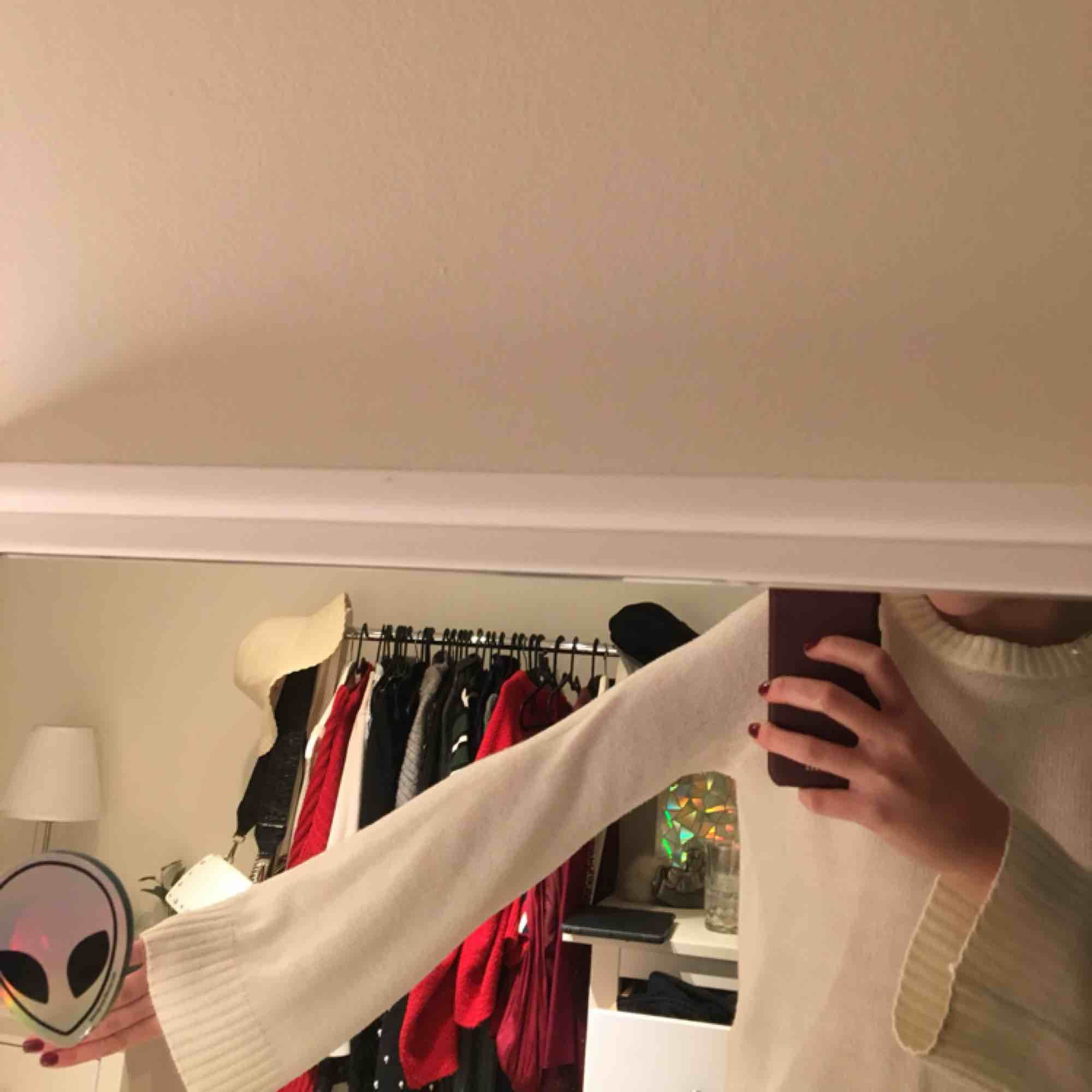 Vit stickad tröja med utsvängda ärmar . Stickat.