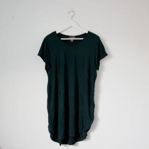Tshirt klänning i en fin mörkgrön färg med lite slits på sidorna. Använd en gång! Frakt tillkommer.
