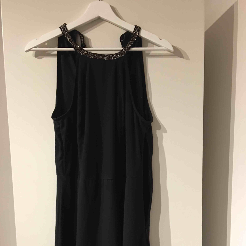 Superfin långklänning. Den är svart och har en markering ovanför midjan så den hänger inte bara rakt. Det är en inner kjol som går precis ovanför knäna och den är i spets. Slits är det på sidan också. Använd 1 gång. Ryggen är öppen.. Klänningar.