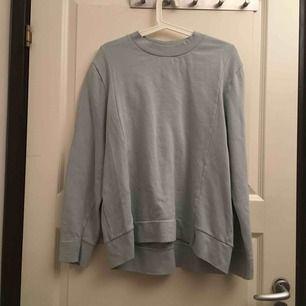Ljusblå långärmad tröja. Färgen är skev på bild, men det är en fin pastellblå färg. Aldrig använd, storlek M hos herr och antagligen L hos kvinnor.
