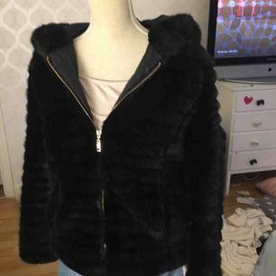 """En svart fake päls köpt på miinto.se. Jackan är i fin kvalité och den är absolut en vinterjacka då den är väldigt varm. Jackan har guldiga detaljer och en luva, den är lite """"randig"""" i päls alltså är den inte helt slät."""