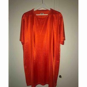 Orange (ser lite mörk ut på bilderna) stor tisha/t-shirtklänning i glansigt material. Använd 1 gång! Frakt tillkommer.