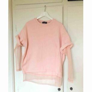 Ljusrosa avklippt sweatshirt med insydd mesh undertill. Köpt på Asos, använd ett fåtal gånger. Finns ett litet litet märke där fram på tröjan, se tredje bilden. Frakt tillkommer!