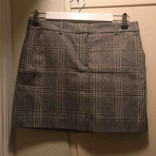 Kort Mango tweed kjol i grå/brunt rutmönster. Lite ull i tyget och passar bra under höst och vinter.