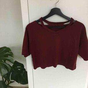 En jättefin mörkröd croppad tshirt! Den har typ öppningar på axlarna vilket är en fin tuch så det inte bara är en vanlig tröja! Passar till allt! Köparen står för frakt