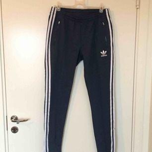 Blå oanvända byxor/leggings från Adidas, mellanhög midja. Möts i Stockholm efter överenskommelse eller skickas mot fraktkostnad.