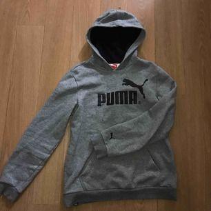 En puma hoodie med luva. Har 2 pytte små fläckar som knappt syns (se bild 1) tror man kan få bort av rätt tvättning.