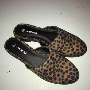 Oanvända slip on skor från Monki med leopardmönster. Strl 40.  Om du önskar få dem levererade tillkommer frakt på 50kr.