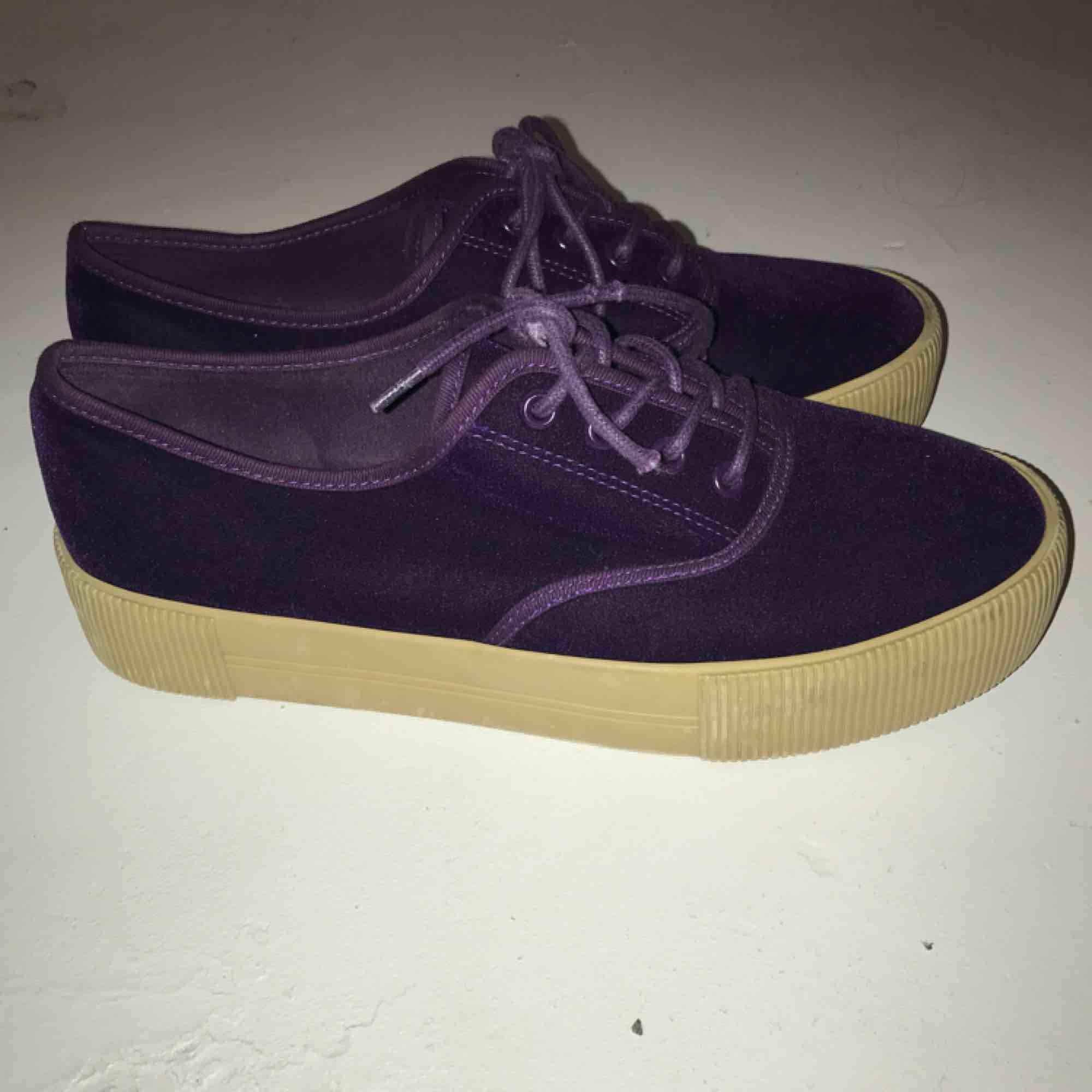 Oanvända sneakers i lila plysch-aktigt material. Från Monki. Strl 40.  Om du önskar få dem levererade tillkommer frakt på 60kr.. Skor.