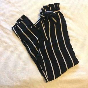 Svarta paperbagbyxor med vita ränder från H&M. Höga i midjan med knytband. Strl 32/XS aldrig använda, tags kvar. Kan mötas upp i Örebro eller skicka mot fraktavgift.