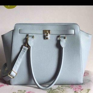 Jättefin väska från Don Donna som tyvärr aldrig kommit till användning. En rymlig väska som är blå/grå med gulddetaljer. Skinimitation.