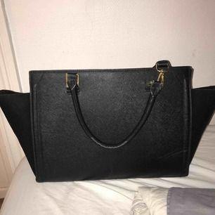 En svart stor väska, får plats med mycket. Aldrig använd men köpt för längesen.