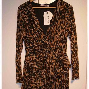 Oanvänd klänning från Na-kd. Storlek M. Leopard Passar från s-l. Hela klänningen får inte plats i en bild. Övre delen av klänningen i första bilden. Nedre i andra bilden. Stretchigt material. Fraktar endast : 47kr