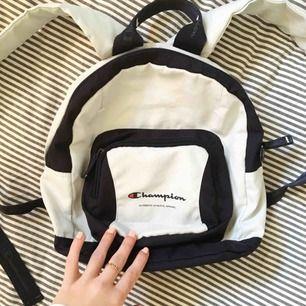En fin liten ryggsäck från Champion, 90-tal. Den är vit med mörkblå detaljer. Har en pyyyytteliten rosa fläck (se bild 2) men det är verkligen inget man ser om man inte kollar noga. Annars i jättebra skick!