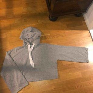 Croppad hoodie med lite utsvängda armar från monki! Superbra skick o knappt använd, frakt tillkommer