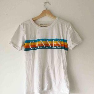 """Vit t-shirt med trycket """"Cannes"""" över bröstet. 100% ekologisk bomull. I nyskick, använd en gång. Köparen står för frakt eller möts upp i Uppsala 💫"""
