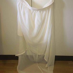 Vit kjol med kort framsida och lång baksida. Nyskick med taggar, säljes pga storleksfel. FRI FRAKT.