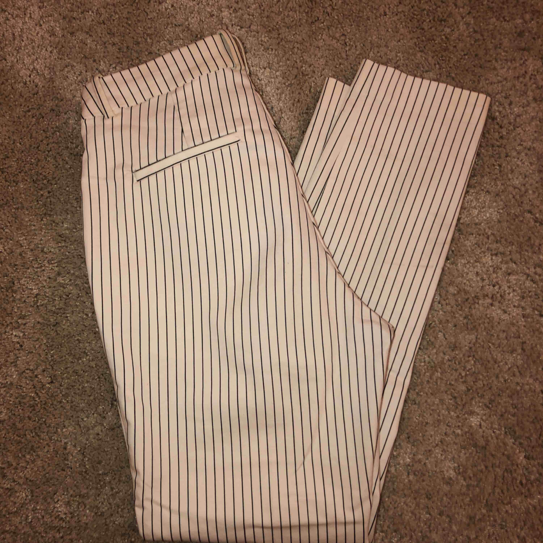 Ett par vita kostymbyxor med svarta ränder ifrån hm. Super  stretchiga och höga i midjan. Nästintill helt oanvända, säljer pga ingen användning utav dem tyvärr. Passar mig som brukar ha S. 💗. Jeans & Byxor.