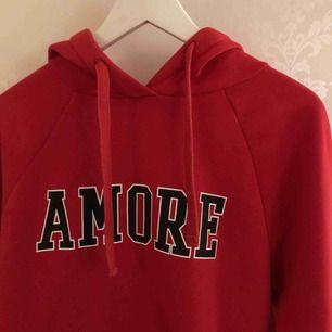 """Röd hoodie med text """"Amore"""". Storlek M men funkar även som en S. Använd ca 2-3 gånger. Säljer pga inte min stil."""