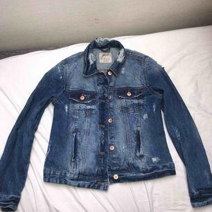 En jeansjacka med slitna detaljer lite överallt, den är i tjockt material. Köpt på Primark i London! Aldrig använd