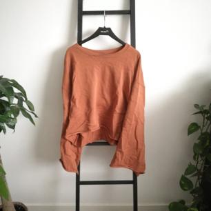 Oanvänd rostfärgad sweatshirt från Weekday med råa kanter och vida armar! Bild två och tre visar färgen bäst. Möts upp i Stockholm eller fraktar för ca 70kr.