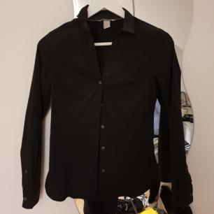 En svart figursydd skjorta i bra skick. Fraktpris tillkommer med 35 kr!