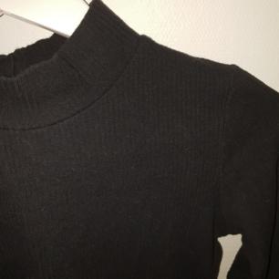 En ribbad långärmad cropad tröja med halterneck från bikbok i väldigt strechigt material. Fraktpris tillkommer med 35 kr!