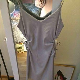 Ribbad kort klänning med öppningar på sidorna