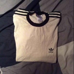 Fin Adidas t-shirt. Varan säljs i befintligt skick. Tröjan är i storlek XL men passar bäst på storlek L eller oversized medium. Fraktkostnad: 50kr. Varan skickas 2 dagar efter betalningen har kommit in på mitt konto. Betalningssätt Swish.