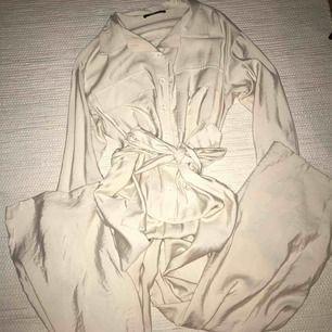 En jumpsuit köpt här på plick från Gina men använder inte. Glansigt beige material i strl. XS men passar även S