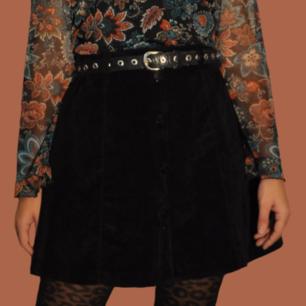 Jättefin kjol I i sammetstyg/suede med knappar fram och bälteshällor. Obs! Läs mått då jag inte är säker på att en engelsk 14 vanligtvis är såhär liten i storleken (kjolen är nog en 36-38 ungefär) Mäter cirka 38-39 mätt tvärs över midjan. Längd: cirka 42-43 cm. Är i begagnat skick men inga synliga brister, fin kvalité! Köparen står för frakten! Samfraktar gärna 👍😊