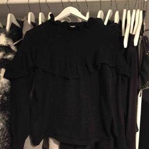 Svart stickad tröja med volanger vid hals, armslut och över bröstet. Fint skick. Köparen står för frakten.