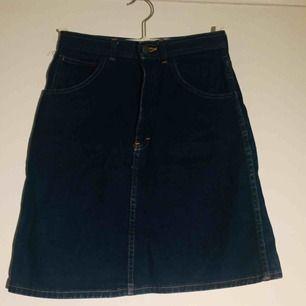 Jeanskjol i mörkblått jeanstyg. Stumt tyg. Ca 52 cm lång, 35x2= 70cm omkrets (35 cm rakt över i midjehöjd). Liten slits rakt bakifrån och två bakfickor samt 2 fickor fram.