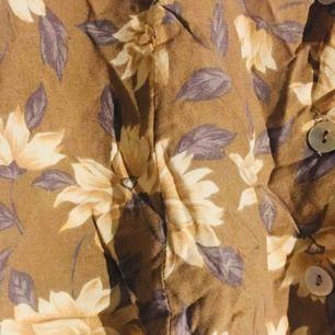"""Söt retro kjol i brunt tyg med blommönster på. Söta pärlemoknappar i sann 60/70-talsstil. 72 cm i omkrets i """"slakt läge"""" i midjan, men är stretch i ett resårband. Kjolen är 45 cm lång totalt från midjan till nedre fåll."""