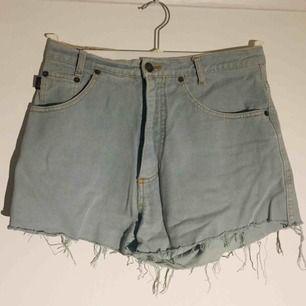 Fransade och supersköna grå/gröna jeansshorts. Strl 31 enligt etikett. Reto och vintageaktig stil. 78 cm i omrets i midjan mätt rakt över. Ca 32 cm långa mätt i yttersömmen på vänster utsida höft/lår.