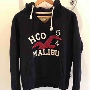 Supersnygg vintage mörkblå hollister-hoodie med tryck, strl M, nyskick!  Finns i Karlstad, kan skickas!