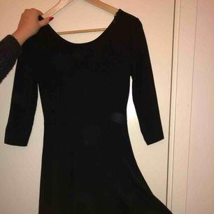 Svart klänning, lite lägre urringning i ryggen än fram. Tight på överkroppen med utsvängd från midjan och ner. Frakt tillkommer!