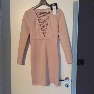 Snygg klänning i strechigt material som ändå slimmar åt! Helt ny. Köpt från Nelly.com