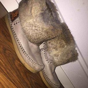 Ett par skor som är gjord av äkta päls och äkta skin jätte fina men har en fläk framme på skorn