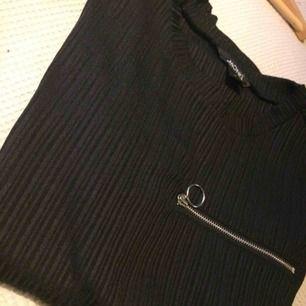 Svart långärmad tröja med struktur och bröstficka. Armarna är lite uppsydda. Fint skick!