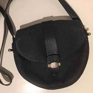 Vintage Dior axelremsväska i modell Honeycomb Canvas Circular Messenger Bag. Med klassiskt Dior mönster i mörkblå.