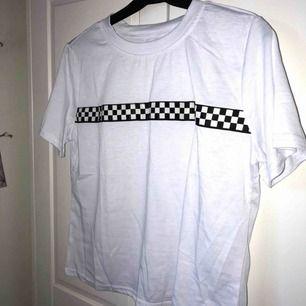 en vit t-shirt med rutigt tryck över bröstet. oanvänd pga att den var för liten (stl L men mindre i storleken)  köparen betalar för frakten :)